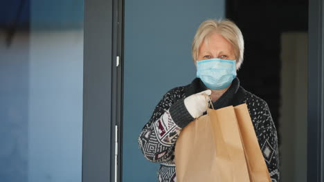 A-Portrait-Of-An-Elderly-Woman-In-A-Mask-Holding-Food-Bags