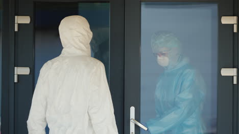 A-Courier-In-A-Protective-Suit-Hands-The-Doctor-A-Red-Case-With-Valuable-Medicines