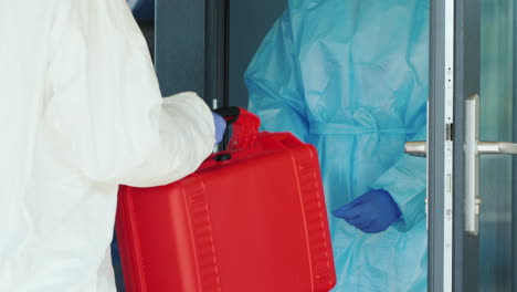 A-Courier-In-A-Protective-Suit-Hands-The-Doctor-A-Red-Case-With-Valuable-Medicines-1
