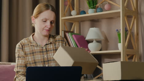 A-Woman-Works-At-Home-Looks-Through-Parcels-Ready-To-Be-Shipped