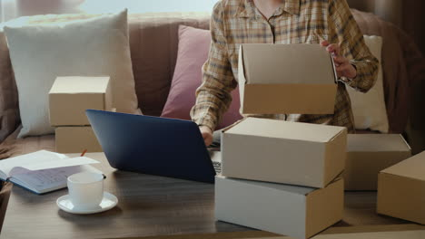 Working-From-Home---A-Woman-Sorts-Parcels-In-Her-Room