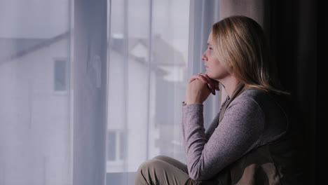 A-sad-woman-sits-on-the-window-sill-looking-out-the-window-at-the-house