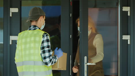 A-courier-wearing-a-mask-and-protective-gloves-delivers-a-parcel