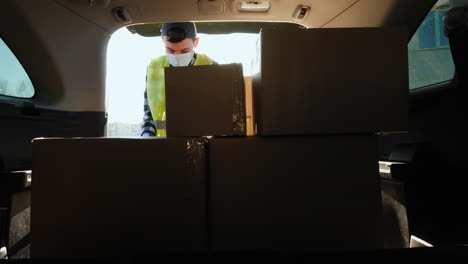 Man-loads-boxes-of-medicines-in-the-trunk-of-the-car