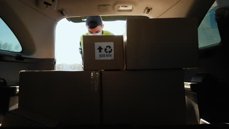 Person-in-a-mask-loads-boxes-of-medicines-in-the-trunk-of-the-car