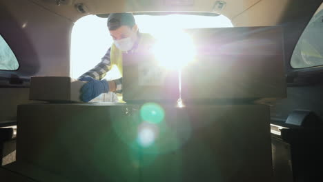 A-young-man-in-a-medical-mask-loads-boxes-of-medicines-in-the-trunk-of-a-car