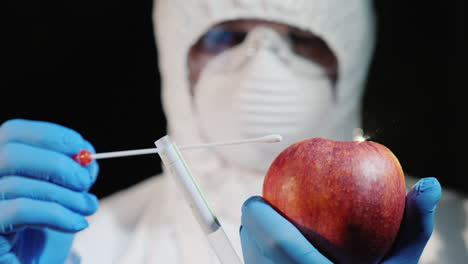 A-man-in-protective-clothing-and-gloves-takes-a-smear-from-a-large-apple