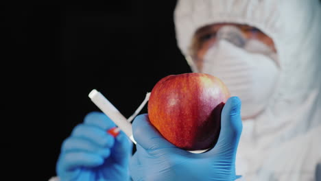 A-man-in-protective-clothing-and-gloves-takes-a-smear-from-a-large-apple-1