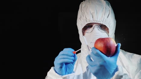 A-man-in-protective-clothing-and-gloves-takes-a-smear-from-a-large-apple-2