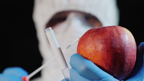 A-man-in-protective-clothing-and-gloves-takes-a-smear-from-a-large-apple-3
