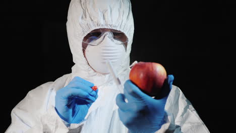 A-man-in-protective-clothing-and-gloves-takes-a-smear-from-a-large-apple-4