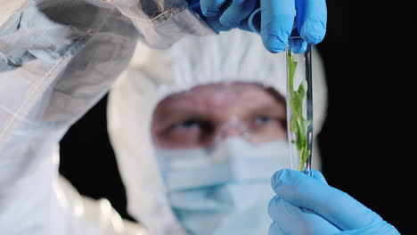 A-researcher-looking-closely-at-a-test-tube-with-a-green-plant