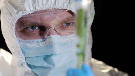 A-researcher-looking-closely-at-a-test-tube-with-a-green-plant-1