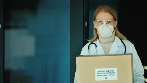 Portrait-Of-A-Female-Doctor-With-A-Box-Of-Protective-Medical-Masks