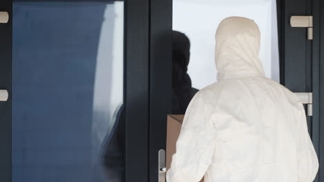 A-Man-In-A-Protective-Suit-Brought-A-Box-To-The-Door