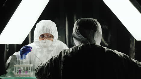 Two-lab-technicians-work-in-the-lab-dressed-in-protective-suits