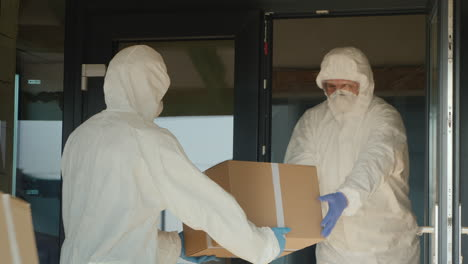 Men-In-Biological-Protection-Suits-Load-Boxes-Of-Medicine-To-Hospital-Warehouse