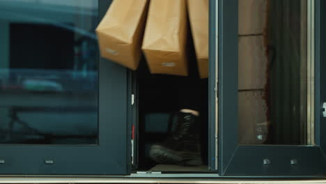 Person-Picks-Up-Food-From-The-Doorstep-Of-The-House