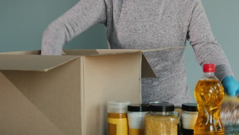 Man-In-Protective-Suit-Packs-Grocery-Set-Into-Cardboard-Box