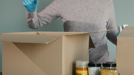 A-Woman-In-Protective-Gloves-Packs-Food-Into-A-Cardboard-Box-For-Shipment
