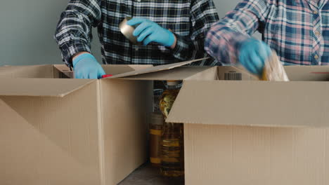 A-Group-Of-Volunteers-Packs-Food-Into-Cardboard-Boxes-For-Delivery