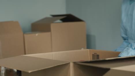 Volunteer-Prepares-Food-Kits-By-Packing-Canned-Goods-In-A-Cardboard-Box