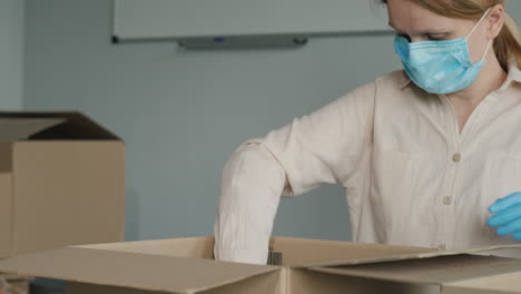 A-Woman-In-A-Mask-And-Gloves-Packs-Food-Into-Cardboard-Shipping-Boxes