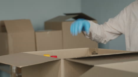 Volunteer's-Hands-Wearing-Protective-Gloves-Put-Food-In-A-Shipping-Box