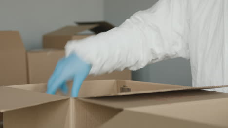 A-Person-In-Protective-Gloves-Packs-Food-Into-A-Cardboard-Box