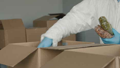 A-Man-In-A-Protective-Suit-And-Gloves-Packs-Food-In-Boxes