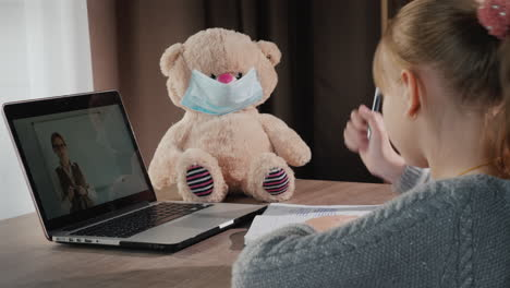 A-Child-Listens-To-An-Online-Lesson-At-Home