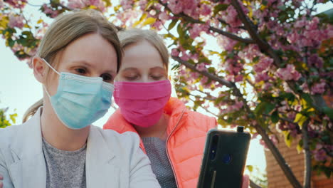 Mother-And-Daughter-In-Protective-Masks-Take-Pictures-Of-Themselves-Against-The-Background-Of-Cherry-Blossoms