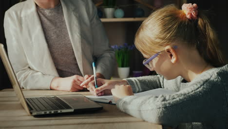 Woman-Helps-Child-With-Homework-As-The-Girl-Studies-Near-A-Laptop