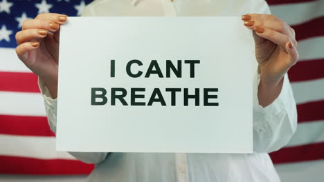 Woman-Holds-Poster-Stating-I-Cant-Breathe-On-American-Flag-Background