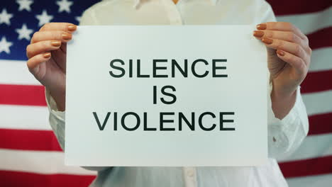 Woman-Holds-Poster-Stating-Silence-Is-Violence-On-American-Flag-Background