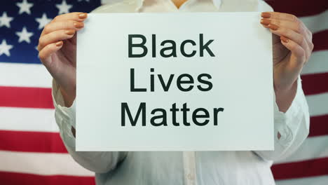Woman-Holds-Poster-Stating-Black-Lives-Matter-With-An-American-Flag-Background