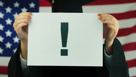 Graduate-Holds-A-Poster-With-An-Exclamation-Point-Against-The-Background-Of-The-American-Flag