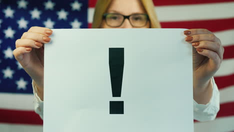A-Woman-Holds-A-Poster-With-A-Exclamation-Mark-Against-The-Background-Of-The-American-Flag