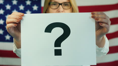 A-Woman-Holds-A-Poster-With-A-Question-Mark-Against-The-Background-Of-The-American-Flag