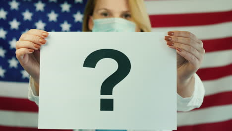 A-Woman-In-A-Medical-Mask-Holds-A-Poster-With-A-Question-Mark-Against-The-Background-Of-The-American-Flag-1