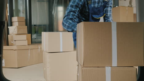 Wholesale-Warehouse-Worker-Loads-Cardboard-Boxes-Into-The-Trunk-Of-A-Van