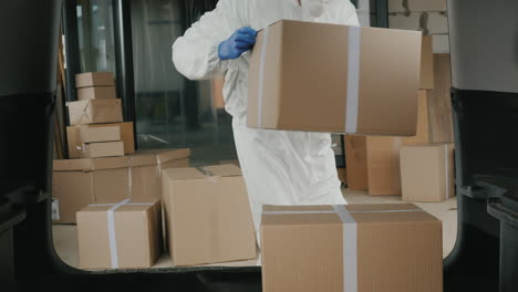 Worker-In-Protective-Clothing-Loads-Boxes-Of-Medicine-Into-The-Trunk-Of-The-Car