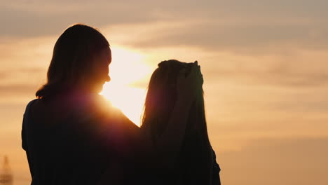 A-Woman-Gently-Kisses-Her-Daughter-Silhouettes-Against-The-Sky-Where-The-Sun-Sets