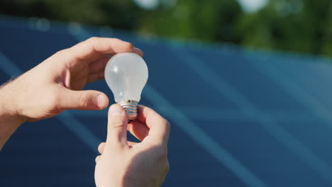 Man-s-Hands-Hold-A-Light-Bulb-Against-The-Background-Of-Solar-Panels