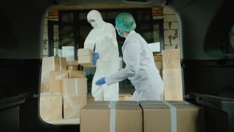 Movers-In-Protective-Suits-Load-Cardboard-Boxes-With-Medicine-Into-The-Car