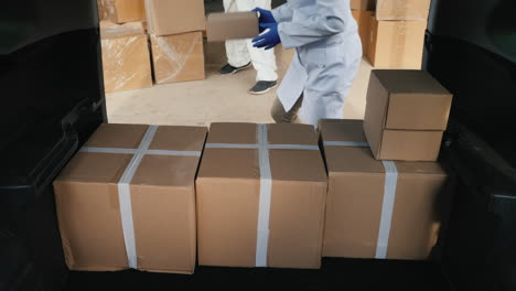 Movers-In-Protective-Suits-Load-Cardboard-Boxes-With-Medicine-Into-The-Car-1