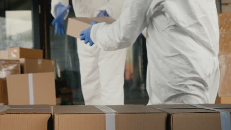 People-In-Protective-Suits-Unload-A-Van-With-Boxes