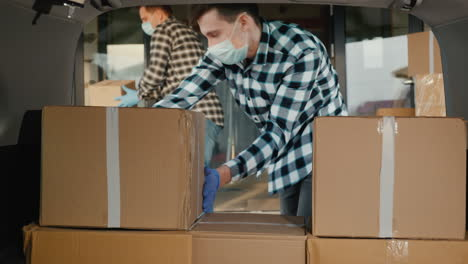 Carriers-In-Protective-Masks-Load-Cardboard-Boxes-Into-The-Trunk-Of-The-Van