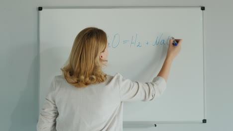 Woman-Writes-Chemical-Formulas-On-Board
