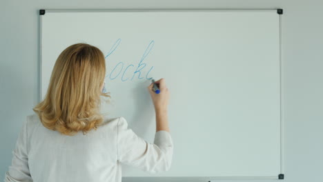 A-Woman-Writes-A-Word-Lockdown-On-The-Class-Board